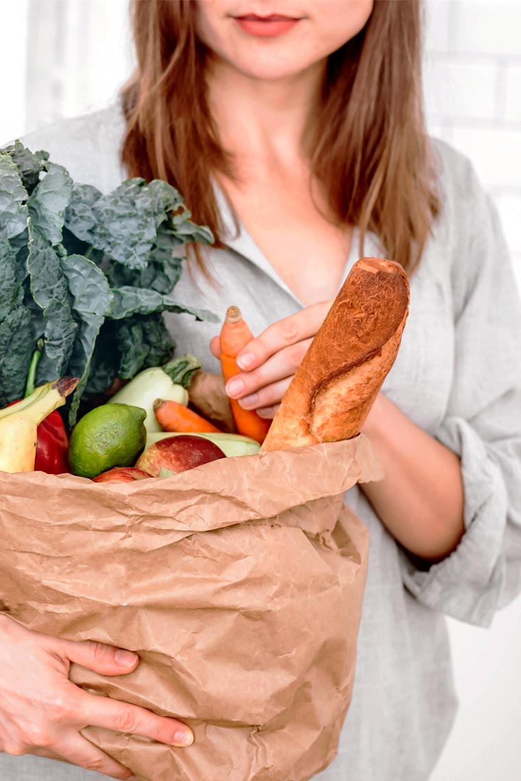 brown haired woman holding a paper bag with different vegan groceries such as bread, carrots, banana, apples and leafy greens
