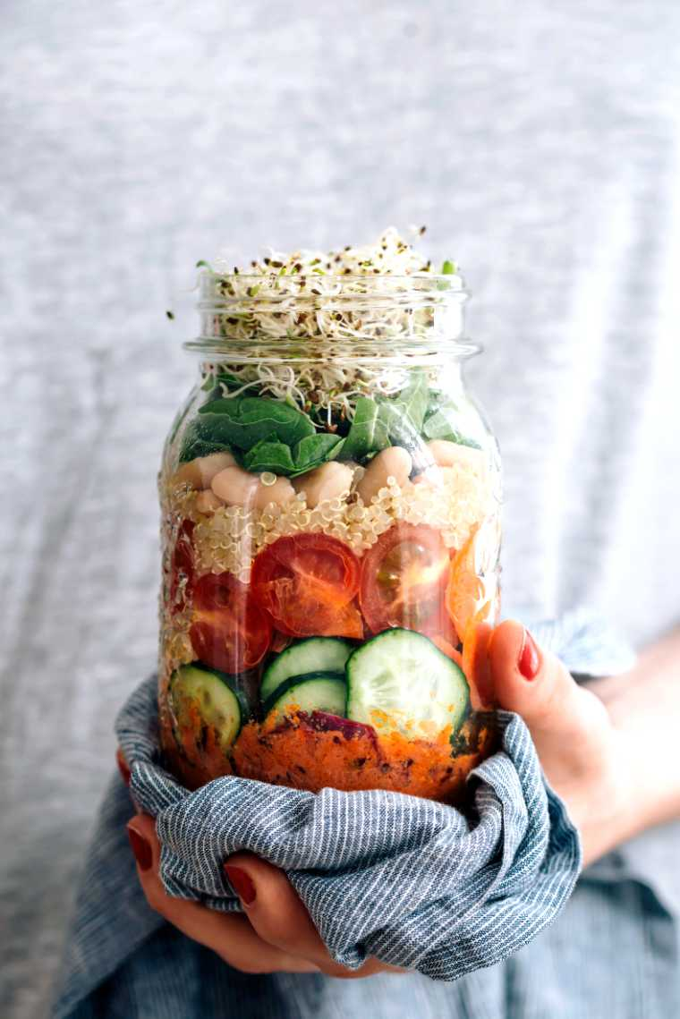woman in grey shirt with red nails holding a mason jar with quinoa, white beans, cucumber, tomatoes, greens and sprouts