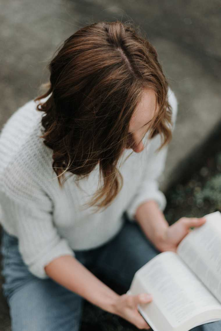 Brown haired woman with cozy white sweater sitting outdoors reading a book