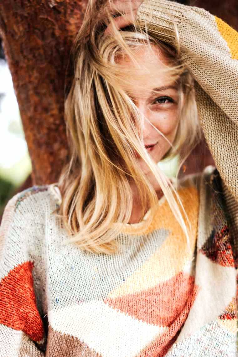 woman with blonde hair and a warm sweater standing in front of a tree and smiling