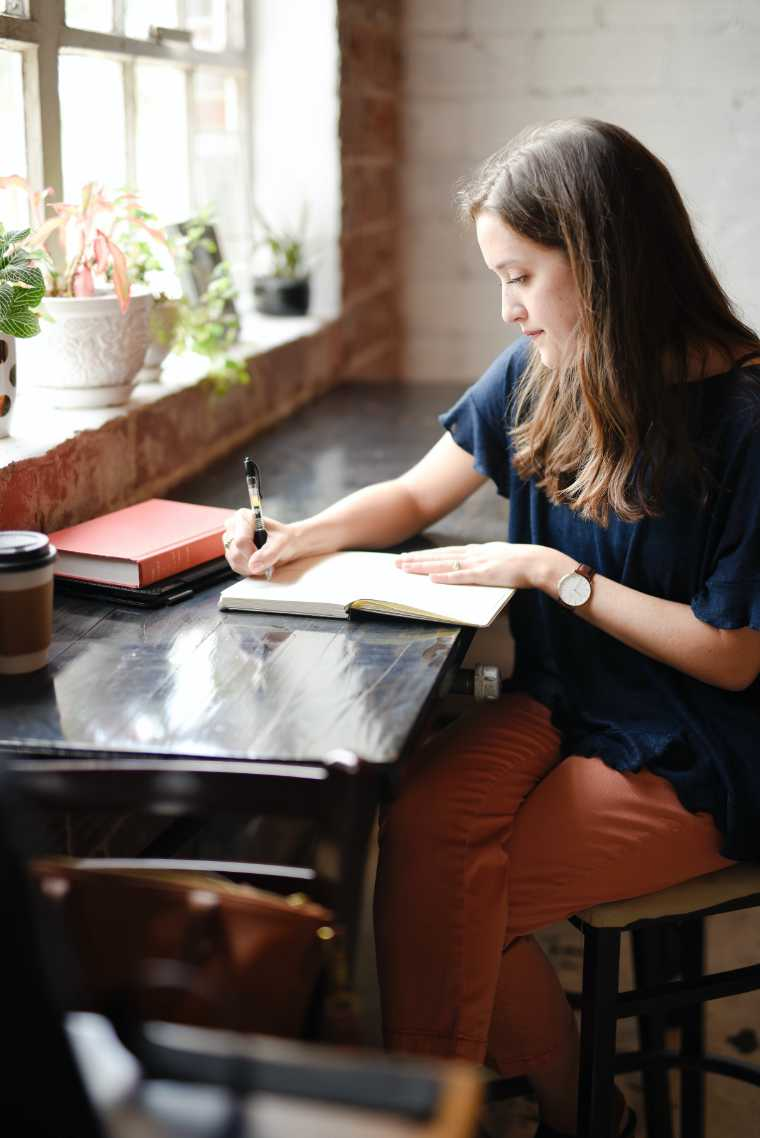 Woman sitting on a table near a bright window, writing in a journal