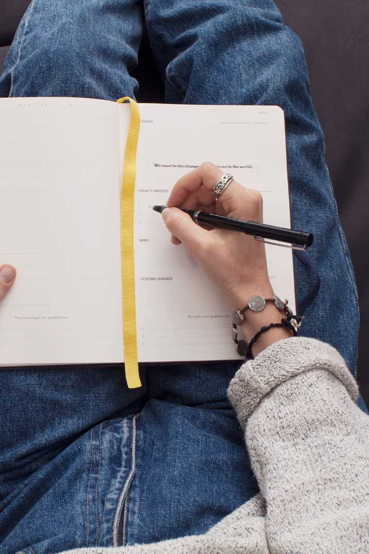 Top view of woman with blue jeans and bracelets writing in her journal