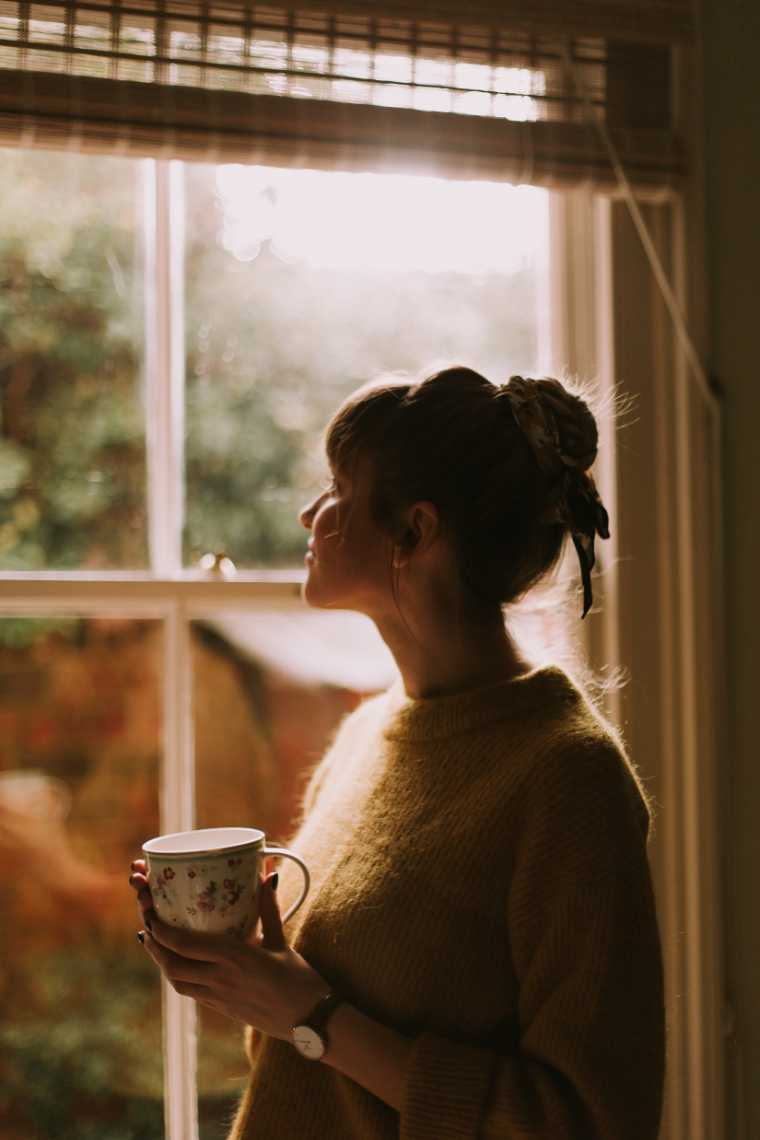 Woman next to window holding cup of tea with warm sunlight coming in