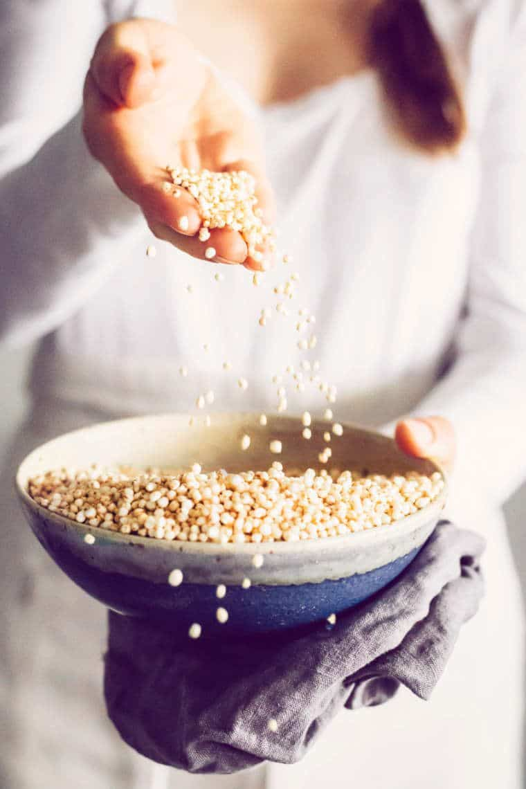 brown haired woman in white shirt and apron holding a bowl of puffed quinoa