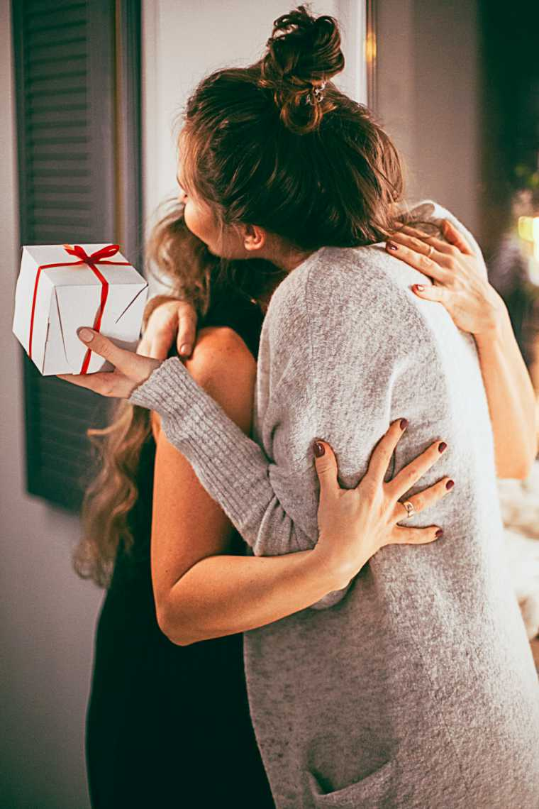 Two women hugging each other, one of them with Christmas gift in her hand