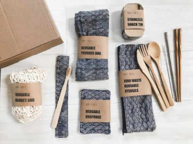 set of bamboo cutlery, reusable bags, straws and snack tin next to a carton