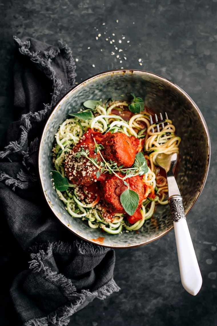 Top view of finished zoodles with black bean meatballs dish presented in a bowl with fresh herbs and some zoodles rolled around a fork
