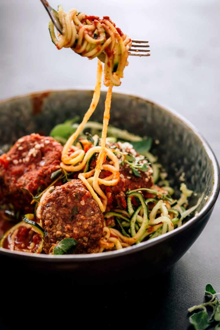 Closeup of zoodles with marinana and black bean meat balls with some zucchini noodles rolled round a fork