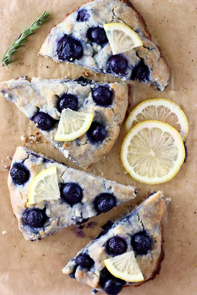 four pieces of gluten free vegan blueberry scones next to some slices of lemon