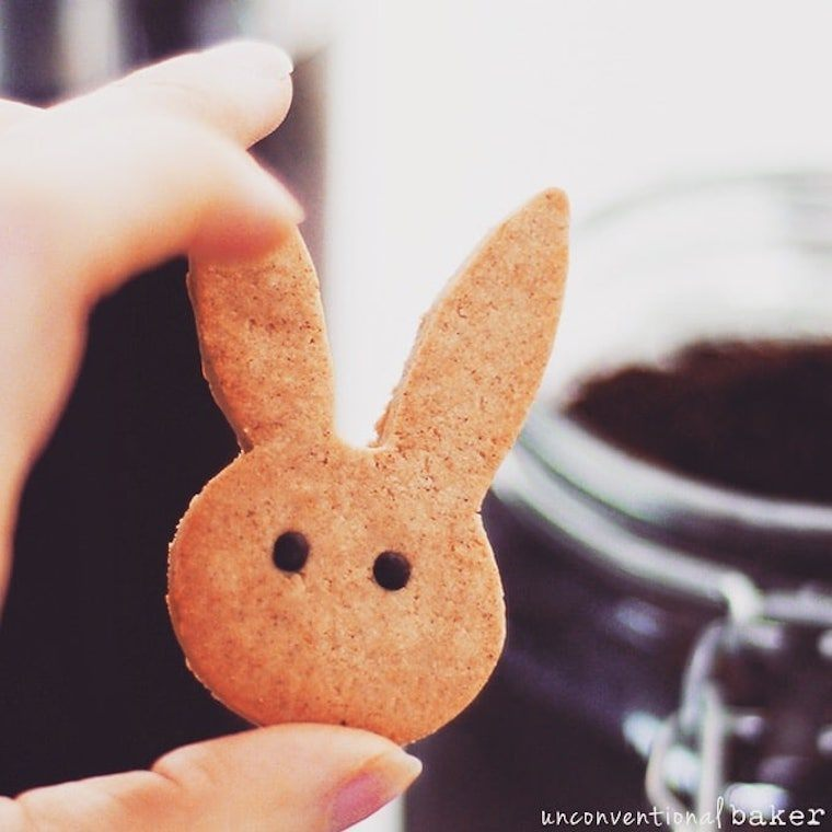 hand holding a vegan cinnamon bunny cookie with eyes as a vegan Easter dessert treat