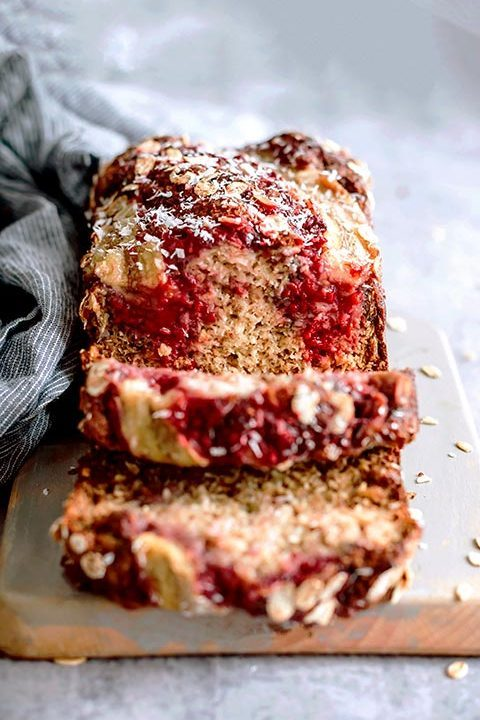 banana bread with raspberry swirl and shredded coconut placed on wooden cutting board