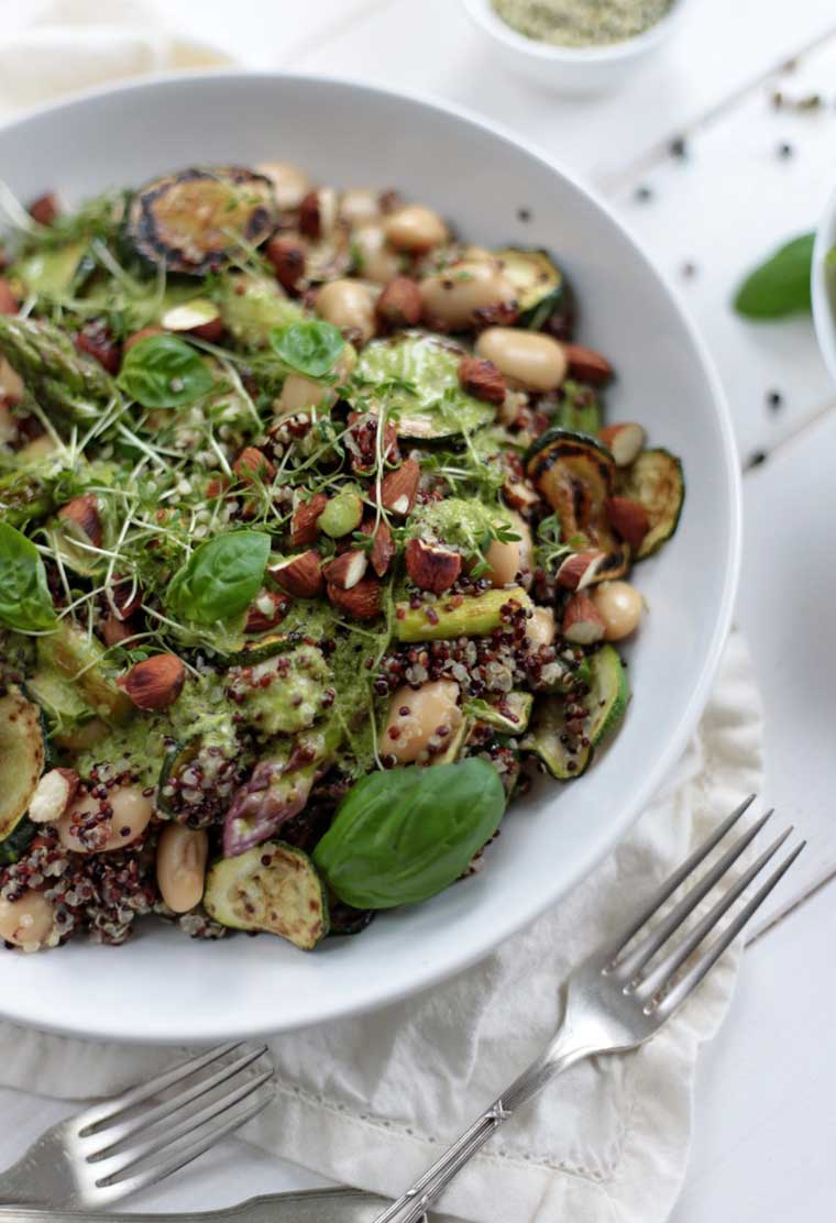 white bowl filled with quinoa, zucchini, asparagus, white beans and fresh herbs as one of the best healthy vegan easter recipes