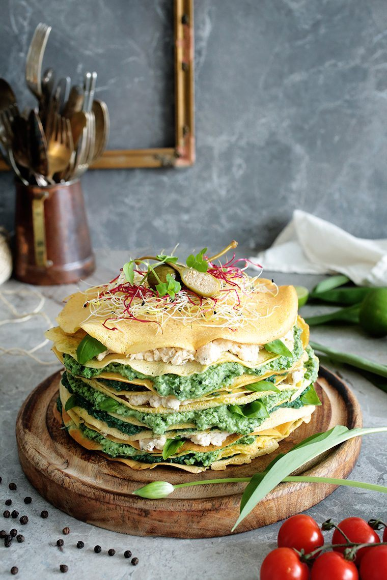 wooden cutting board with a layered savory crepe cake and sprouts