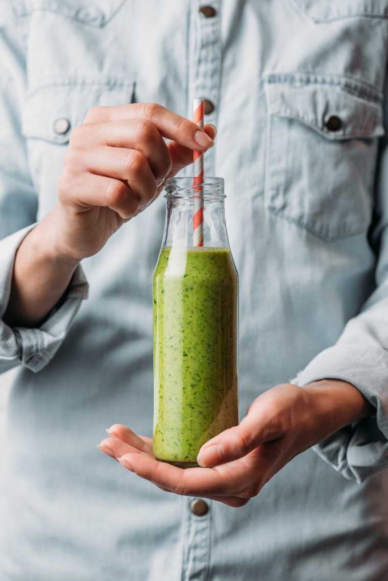 person in jeans jacket holding a tall glass with green smoothie and a straw