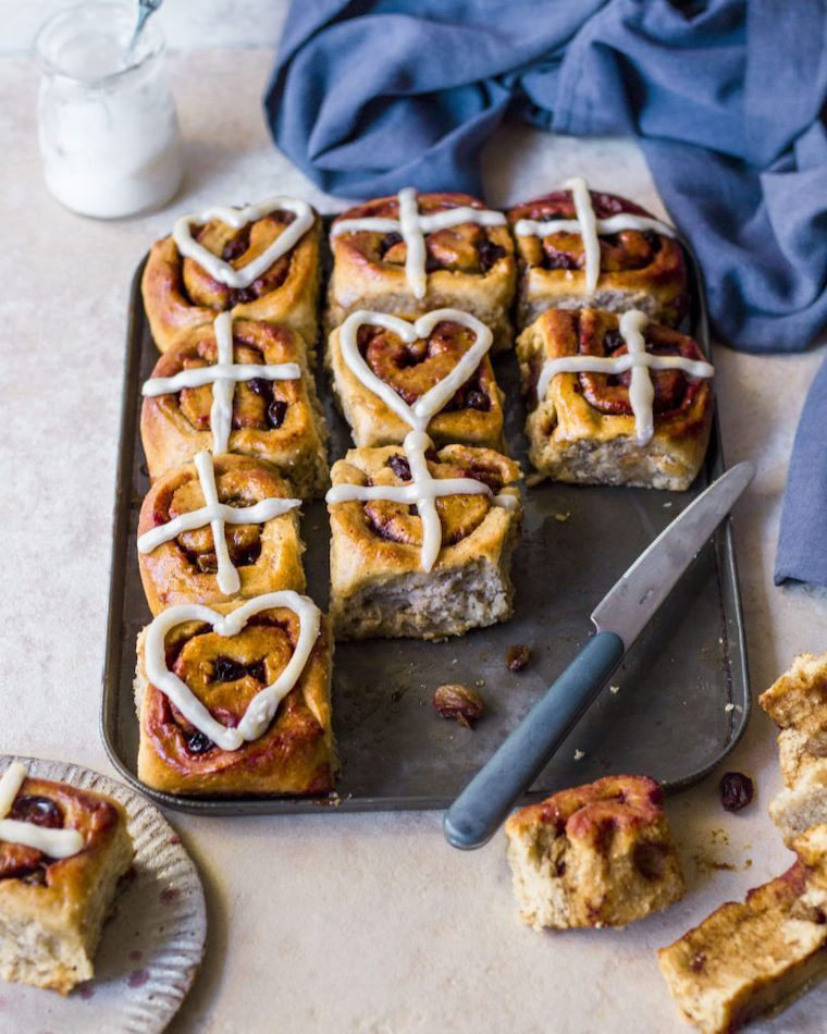 baking dish on a table with a knife and eight vegan hot cross buns cinnamon scrolls