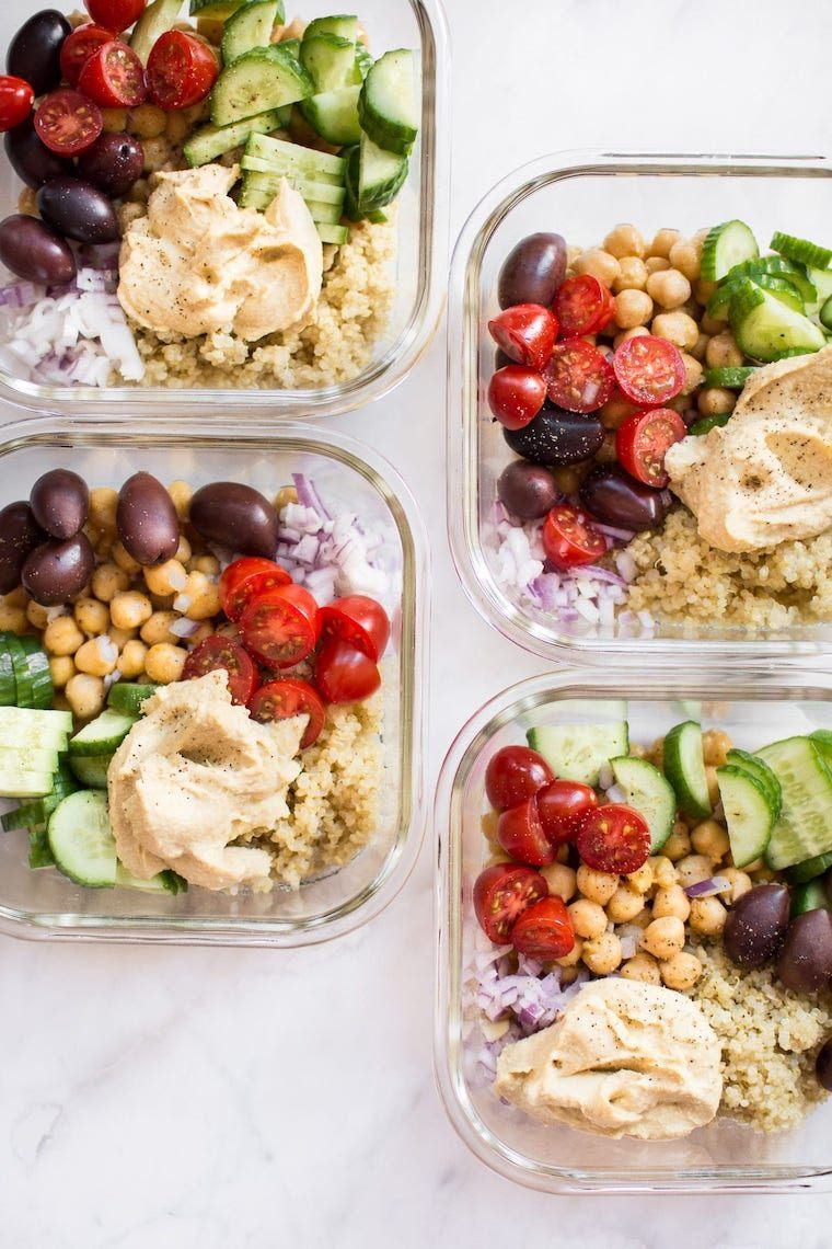 four glass food containers filled with quinoa, chickpeas, olives, tomatoes, onion, cucumber and hummus
