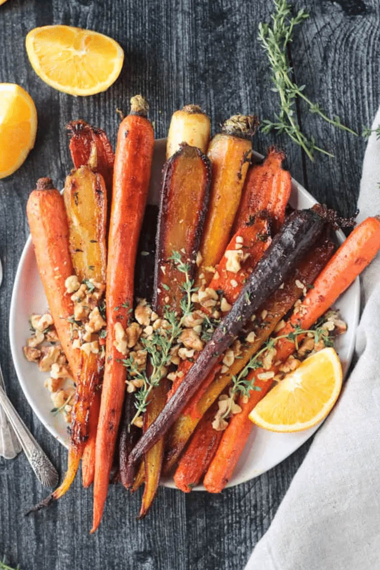 white plate on a wooden table with colorful roasted carrot and nuts