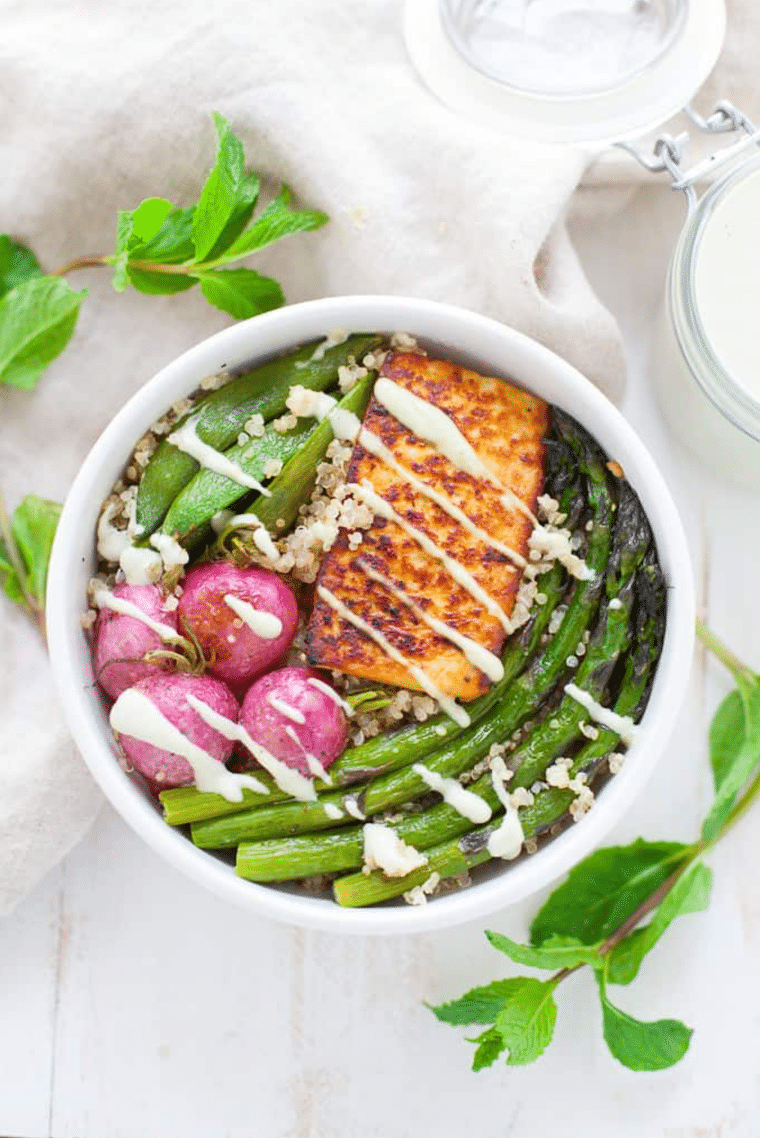 white bowl with quinoa, asparagus, radishes and tofu drizzled with a vegan sauce