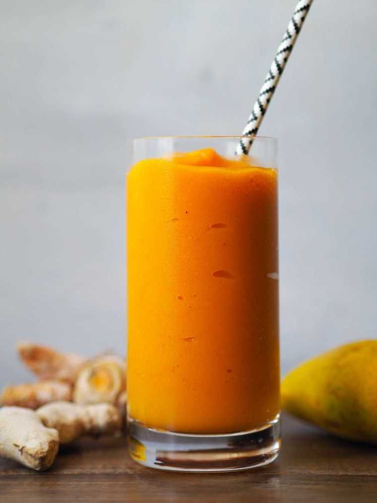 wooden table with fresh mango, ginger and a glass with bright orange plant-based smoothie