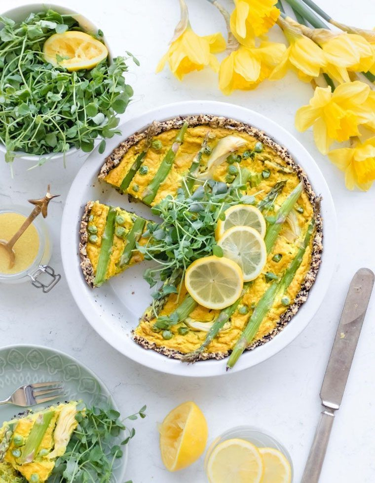 white table with flowers, fresh greens and a white baking dish with a yellow vegan asparagus quiche
