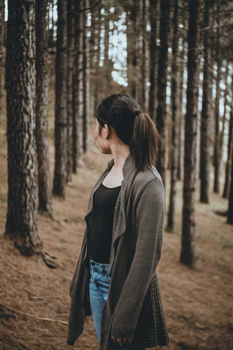 brown haired woman in jeans and woolen cardigan standing in a forest